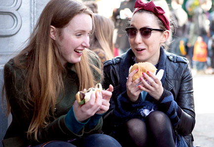 Two young women sitting on the ground, eating burgers