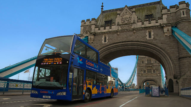 Golden Tours bus tour driving over Tower Bridge