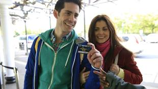 A male and female couple show their London Pass to get into a tourist attraction