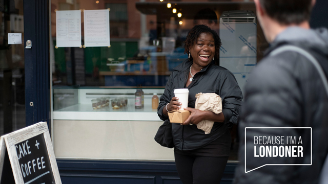 """A lady stands in front of a shopfront with a takeaway coffee cup and food wrapped in a brown paper bag, she's smiling as a man walks past in the foreground. A logo worded """"Because I'm a Londoner"""" is overlaid on the image, inside a speech bubble."""