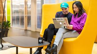Two colleagues sitting on a sofa looking at a laptop in a trendy office