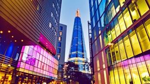 The Shard in the centre of a walkway. There are buildings with pink, blue and yellow glass panels on both sides of the path.