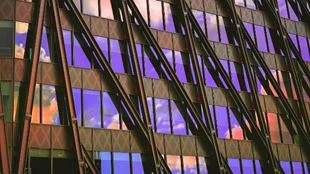 Glass windows of a building reflecting the purple sky and orange clouds.