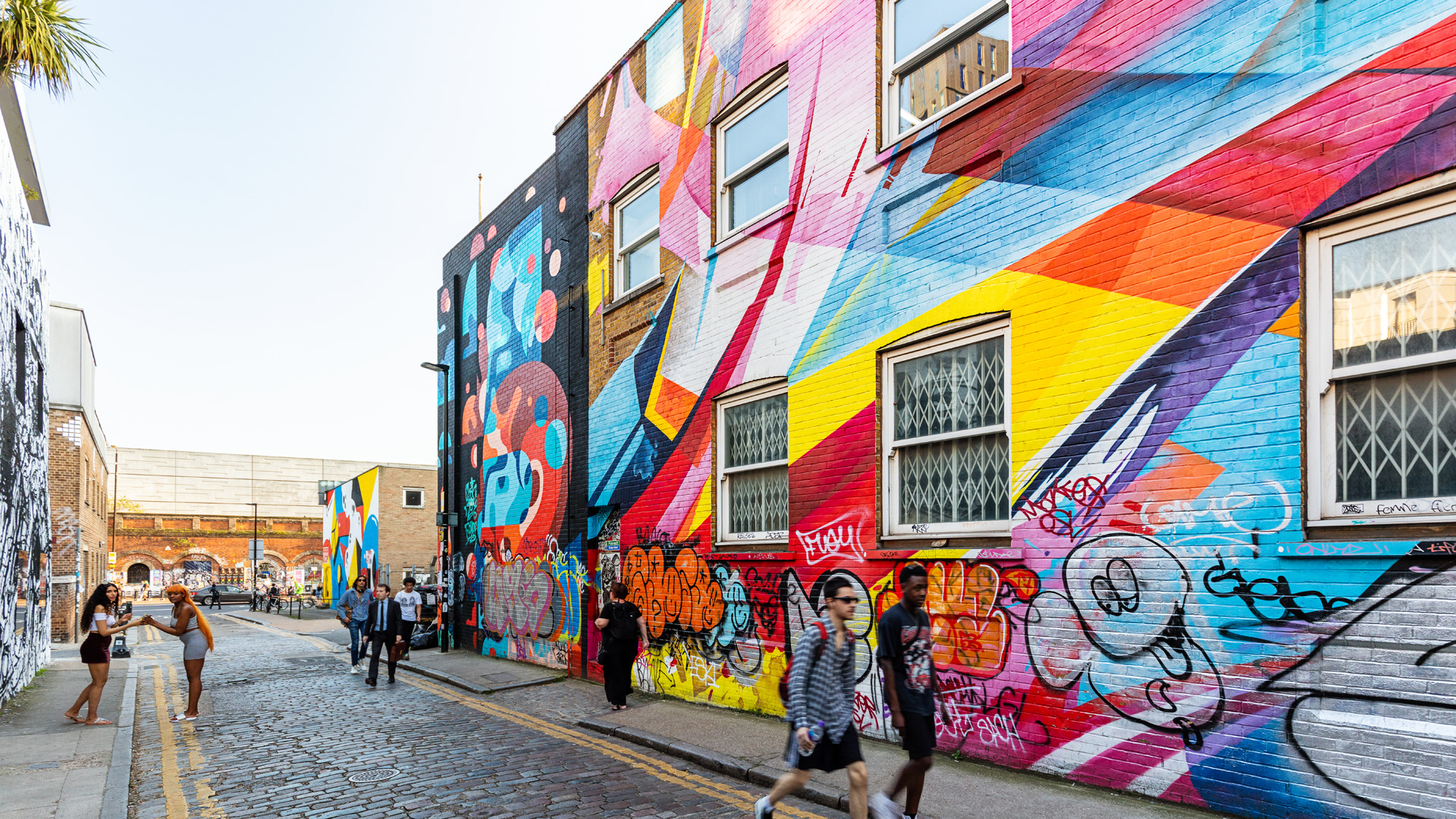 People walking on a cobbled street with buildings covered in bright rainbow coloured graffiti