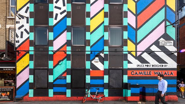 Man walking past the facade of a building painted with vibrant colours by an artist Camille Walala whose name is written on the bottom right corner of the building
