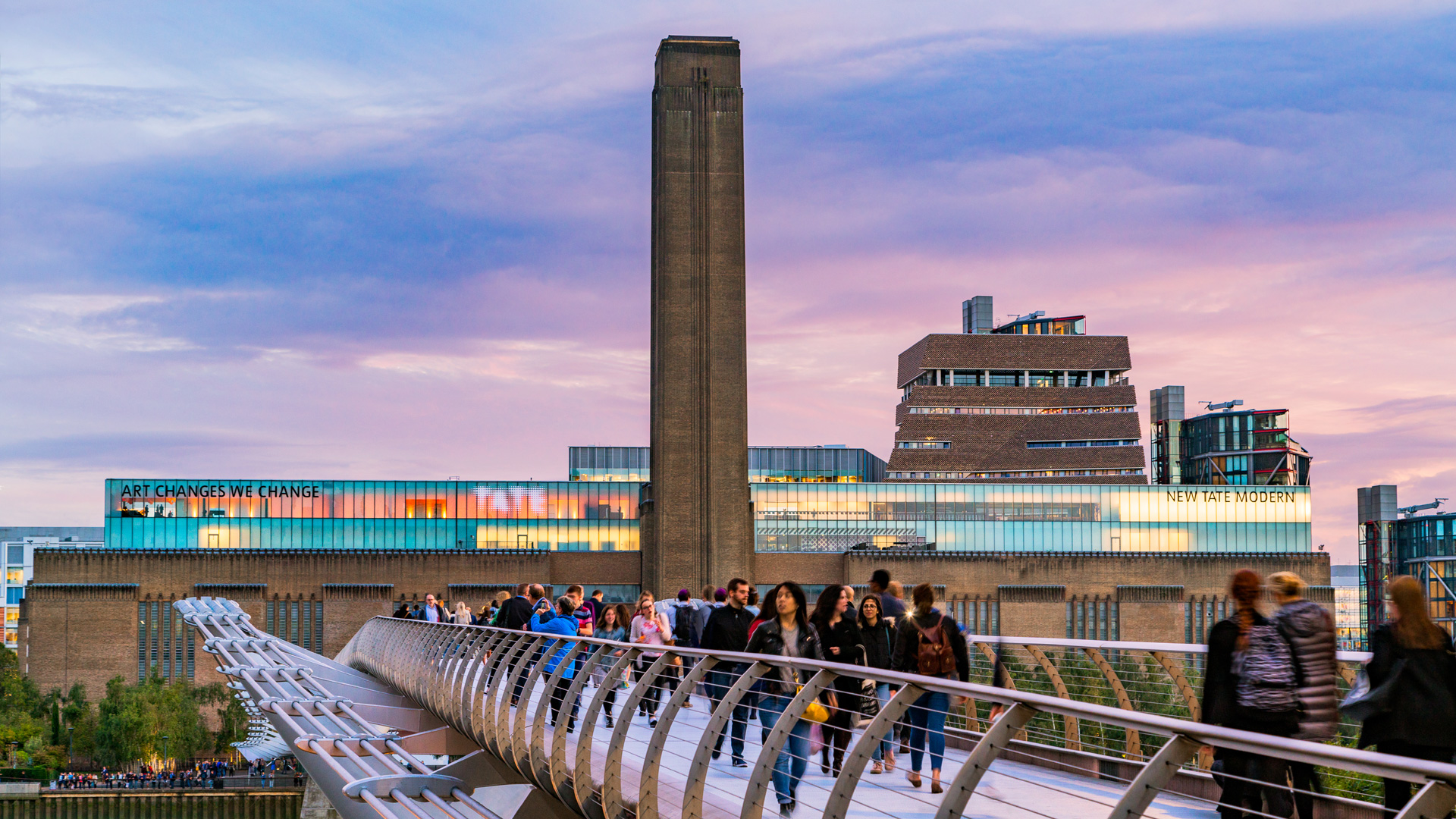 The Tate Modern in the background with people walking across the Millenium Bridge with a violet tinged sky above