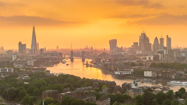 Sunset over the river Thames with orange tones and the city's skyscrapers in the background including The Shard