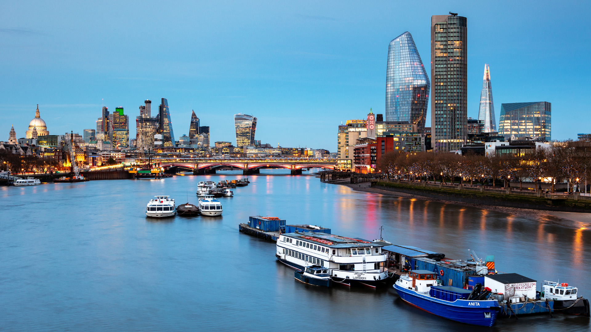 Boats on the river Thames with the tall skyscrapers of the city in the background along with Blackfriars Bridge and St Paul's Cathedral in the distance