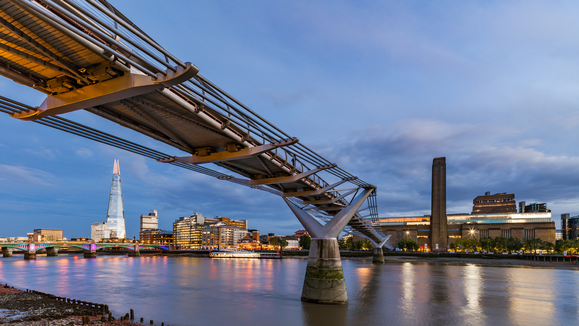 The Millenium Bridge reaching across the Thames to the Tate Modern at dusk with The Shard in the background