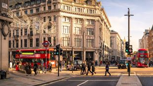 People enjoy the shops on London's Oxford Street during golden hour.