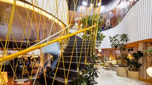 A bright and yellow spiral staircase in one of London's modern co-working spaces.