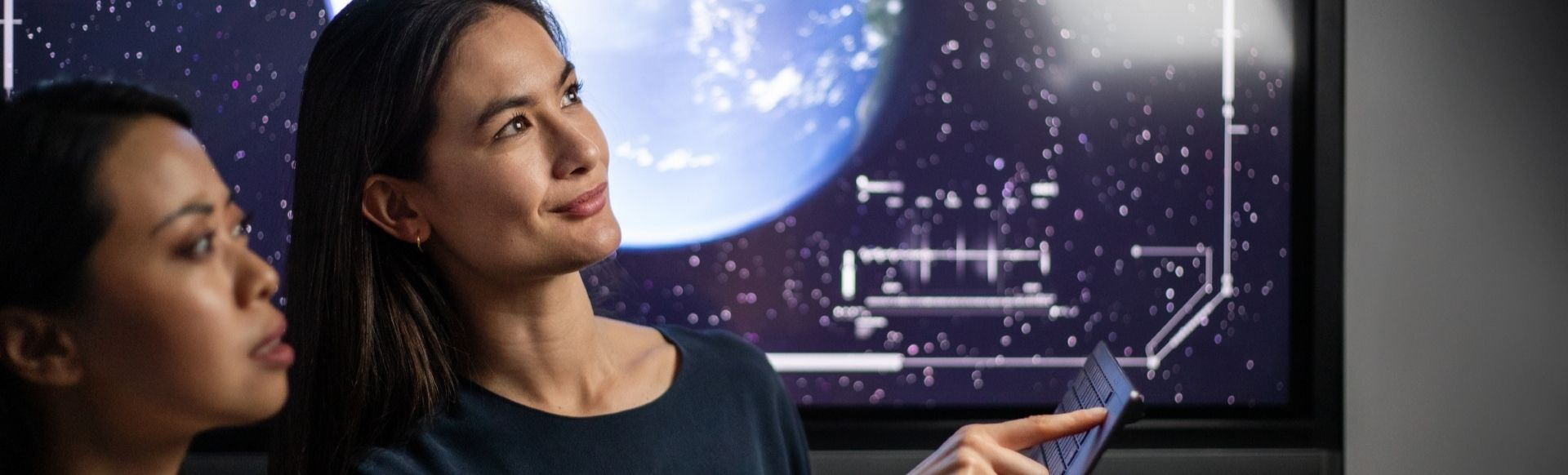 A woman showing another young woman edtech technology with a space background.