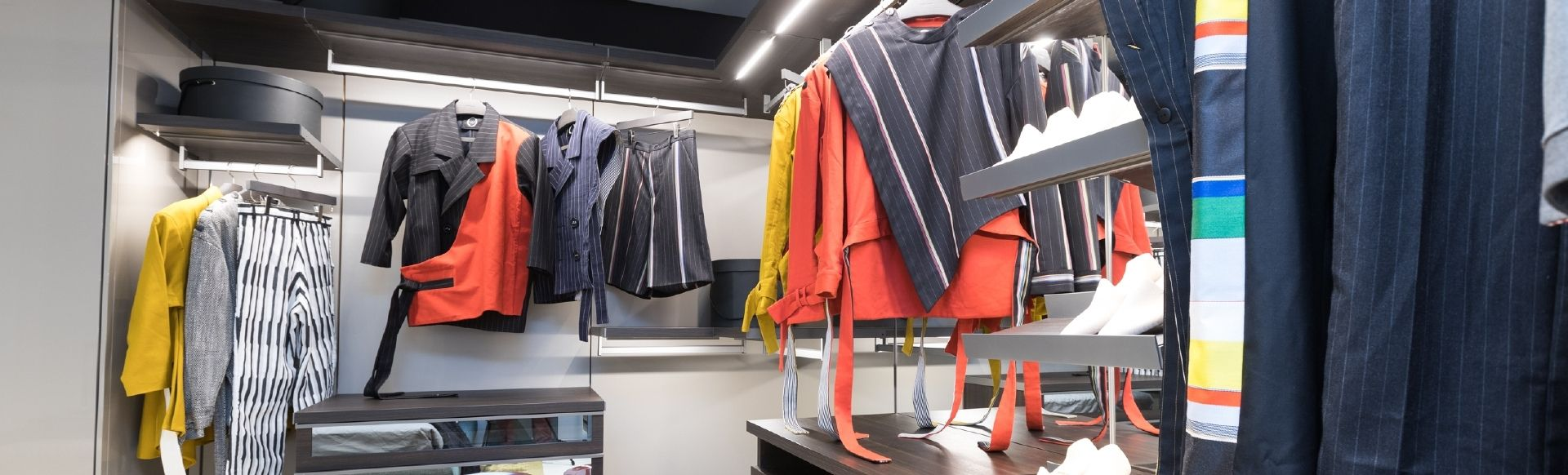Orange, yellow, black and white clothes presented hanging in a wardrobe in Istituto Marangoni.