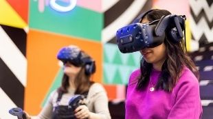 Two women wearing virtual reality glasses and devices to play games.