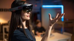 A woman wearing a virtual reality headset with one hand up in the air, focusing on the movements of her fingers.