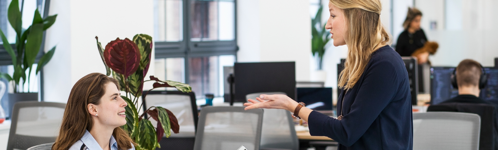 Two colleagues sitting down and chatting in a London office
