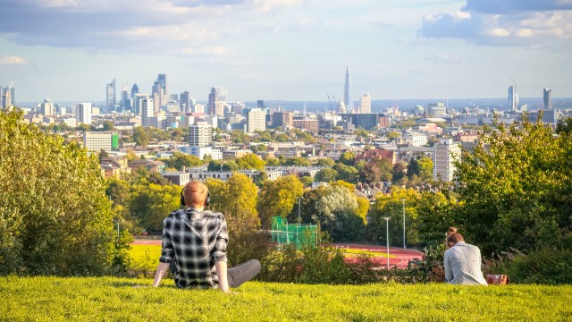 Two people sitting on Parliament Hill on a sunny day looking towards central London
