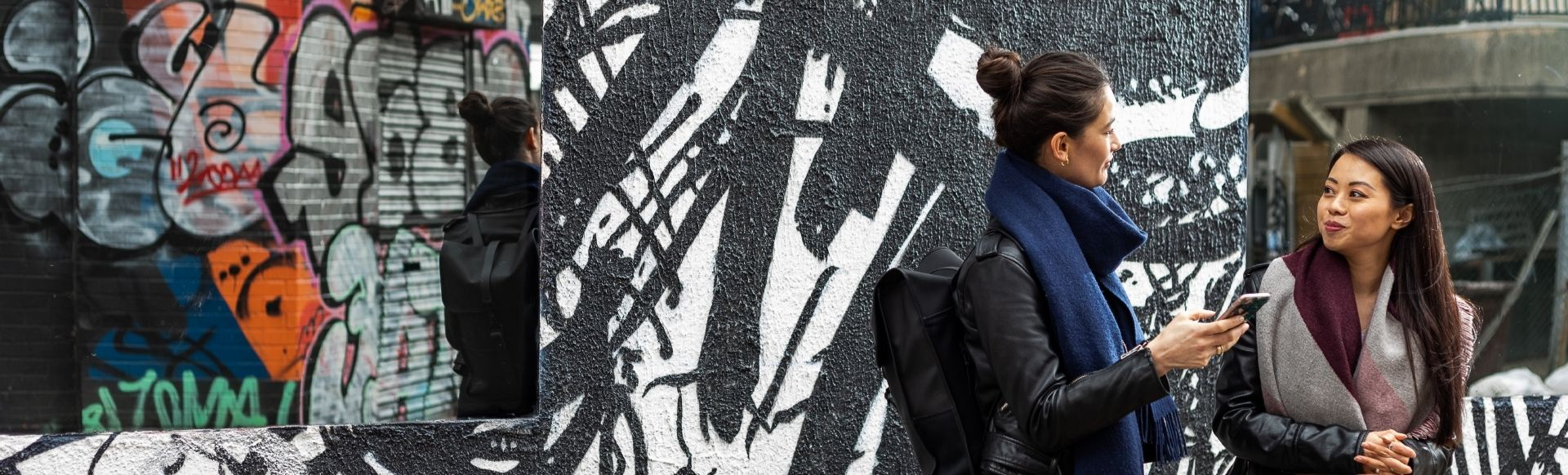 Two young women chatting in front of a streetart wall painted with black and white graffiti.