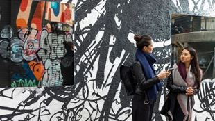Two young women chatting in front of an streetart wall painted with black and white graffiti.