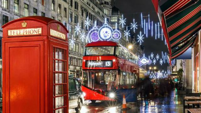 Picture of a traditional red telephone box, red double decker bus with Christmas lights and decorations in the background.
