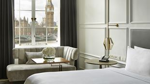 Bright hotel room with an elegant white interior, with a view of the Big Ben and Houses of Parliament.