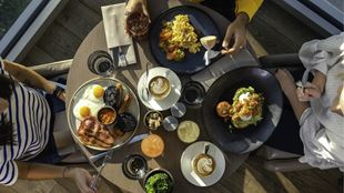 Three brunch plates, coffee and drinks placed on a wooden table, photographed from above.