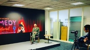 In the CCT venues, a man wearing a grey suit sits in a chair on a small studio stage with a large Comedy poster as a background and is filmed by a camera woman.