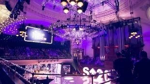 Stand up to Cancer event at Central Hall Westminster; showing a big stage in purple light and a big chandelier in the centre.