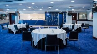 Round table arrangements with white table cloths on blue carpet in the Chelsea FC event venue.