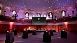 An event venue lit up in purple-orange light showing standing tables covered in dark cloth at Church House Westminster.