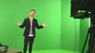 In the Kimpton Fitzroy London studio, a man in a dark suit is standing in front of a green screen with his arms open and talking to the camera.
