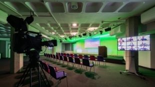 The hybrid event studio at QEII Centre shining in green light. A big studio camera is in the front left corner overlooking empty seats, a small stage and several screens.
