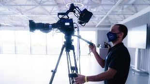 A man wearing a face mask is working behind a film camera in a studio with bright natural light.