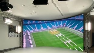 A big wall-to-wall screen inside a studio showing the Twickenham Stadium ground from above.