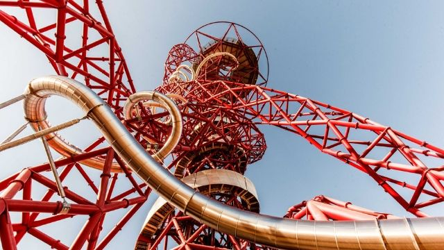ArcelorMittal Orbit, a long tunnel slide within a red metal construct, looking up to the top of the slide.
