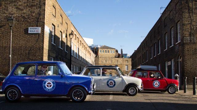 A blue mini car, a white mini car and a red mini car, parked in a row.