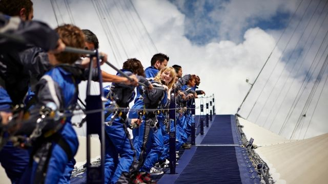 Group of people in a line walking up the roof, holding onto the handrail, wearing blue safety suits.