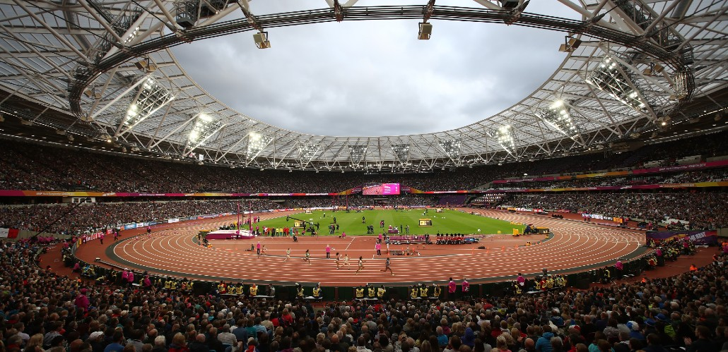 A full audience cheer on athletes as they run to the finish line during a race at the London Stadium