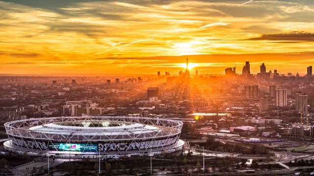 London skyline at sunset with London stadium in the foreground.