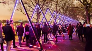 Lumiere London light festival featuring colourful triangles at night with crowds attending.