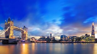 View of Tower Bridge and the Shard in the evening, with a dark blue sky and yellow lights mirroring in the river Thames.