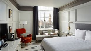 London Marriott Hotel room with white interior, one orange-brown chair and the Big Ben can be seen through the window.