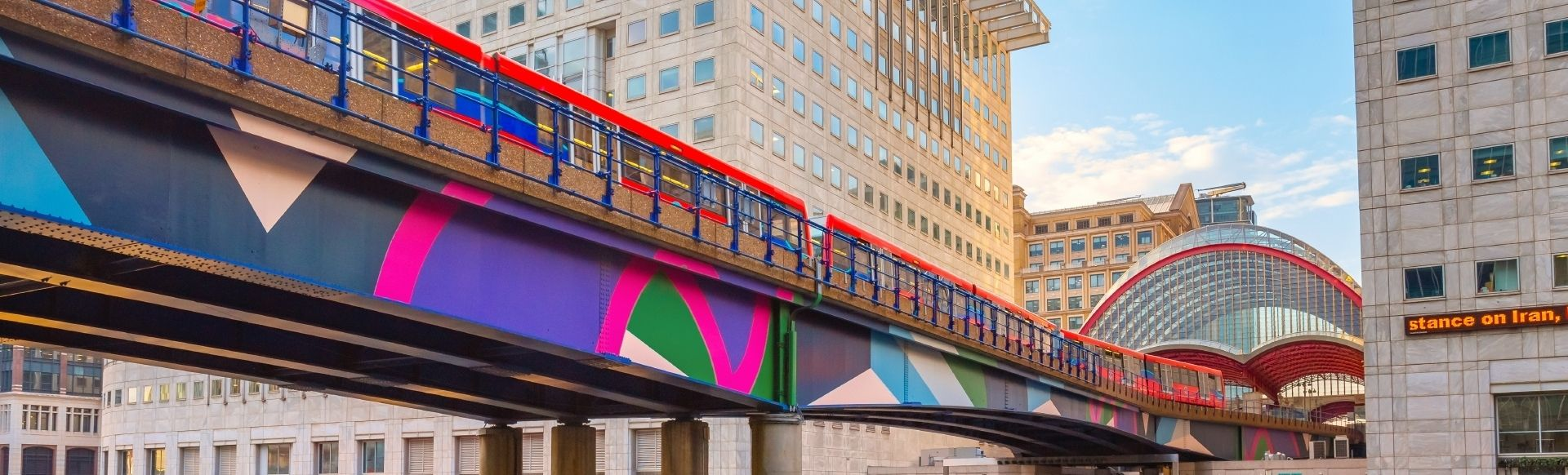 Colourful bridge in Greenwich, Canary Wharf DLR station, with a purple, pink, green and blue pattern on the side. The bridge carries a public transport train and runs in between two buildings.