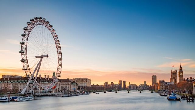 View from the river of the London Eye and Westminster, with the Big Ben during sunset.