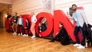 Group of delegates standing next to a giant London installation.