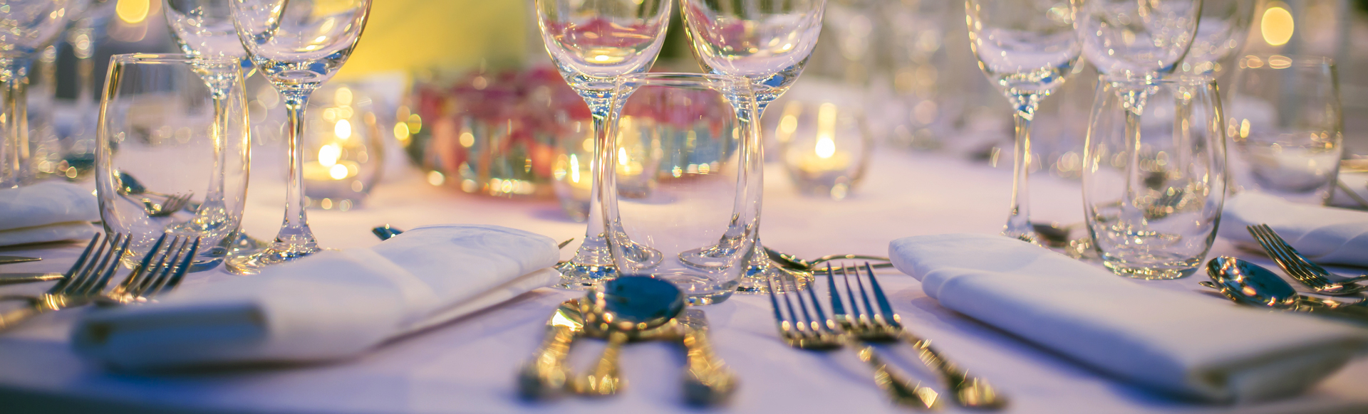 Dinner table close-up, with wine glasses, cutlery and candle lights placed in an elegant setting.