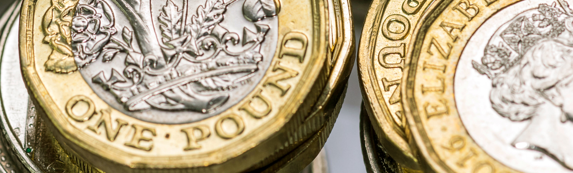 One pound coins stacked on each other.