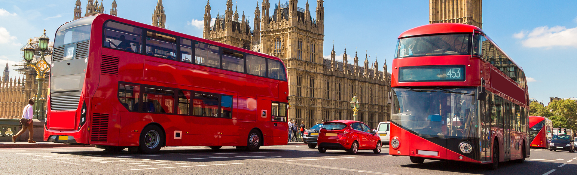 Two red doubledecker buses driving on the main street in front of the Houses of Parliament on a sunny day.