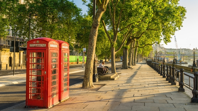 Traditional red phone boxes alongside the river Thames