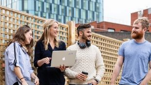 Two women and two men laughing and talking with their laptops in their hands